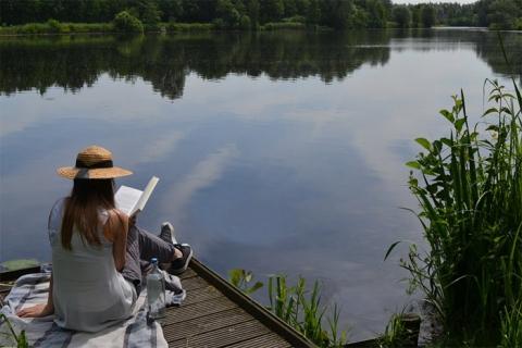 Woman reading book by a lake