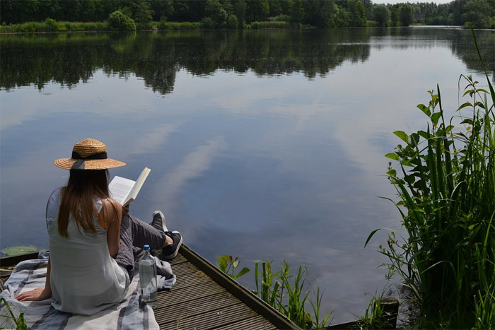 Woman reading book by a lake