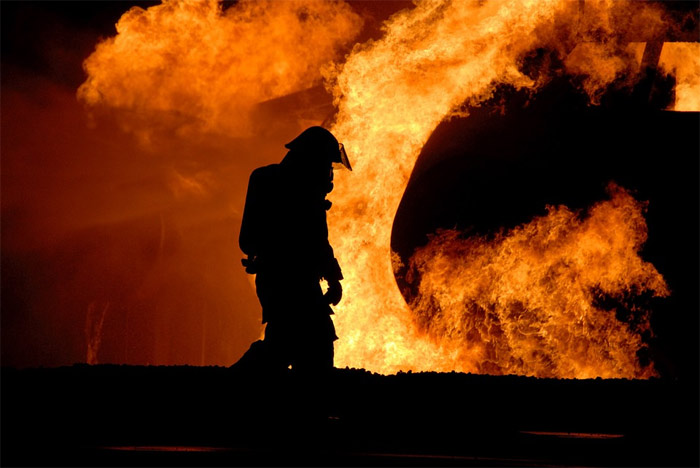 Firefighter in front of house fire